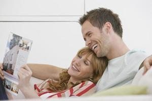 Cheerful couple relaxing on couch reading magazine photo