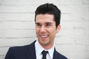 alegre joven en traje de negocios sonriendo al aire libre foto