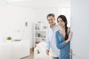 Cheerful couple inviting people to enter in home photo