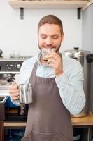 alegre trabajador de café masculino está probando espresso hecho foto