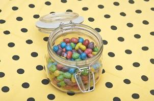 Colorful candies in glass jar on polka dot napkin photo