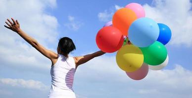 cheering woman with colorful balloons against blue sky photo