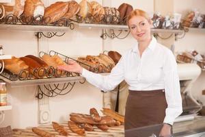 alegre mujer panadero está invitando a su tienda foto