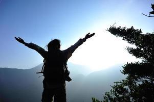 torcendo os braços abertos de alpinista de mulher no pico da montanha