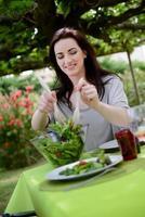alegre joven sirviendo ensalada en fiesta de barbacoa al aire libre foto