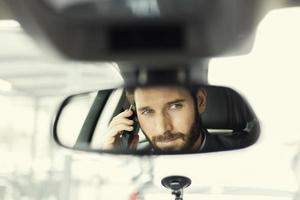 Cheerful man on mobile phone in car mirror reflection