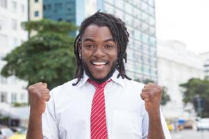 Cheering african american businessman with dreadlocks in the city photo