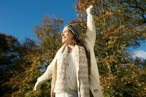 Cheerful woman laughing outdoors on a sunny fall day
