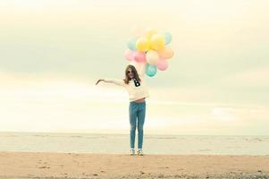 The summer is over. Cheerful girl with colored balloons.