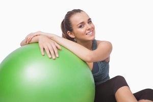 alegre joven sentada junto a una pelota de fitness foto