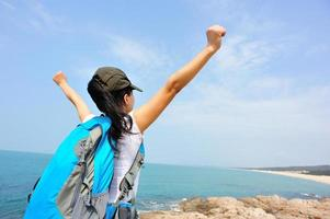 cheering woman hiker open arms at seaside, summer holidays photo