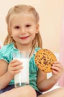 niña alegre con galletas de chispas de chocolate y leche foto