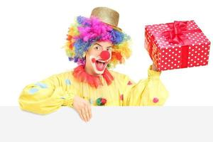 Male clown with cheerful expression holding present behind blank photo