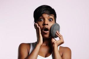 mujer sorprendida con esponja metalick en una cara foto