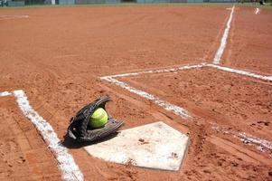 Un guante de béisbol con una pelota en un campo de béisbol foto
