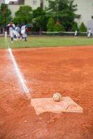 Béisbol y base en el campo de béisbol con jugadores practicando foto