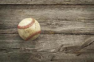 Old baseball on rough wood surface photo