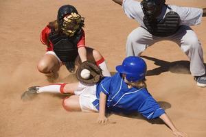 jugador de softball deslizándose en el plato foto