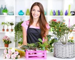 Beautiful girl florist in flowers shop