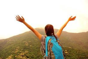 animando senderismo mujer brazos abiertos en el pico de la montaña foto