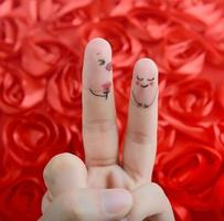 sonriente dedo pintado sobre fondo rojo, concepto de San Valentín. foto