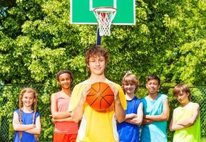 Boy holds ball and his friends standing behind photo