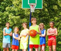 Boy with his team behind during basketball game photo