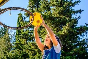 menina de sete anos está jogando basquete