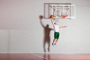 Hombre joven sano y duro jugando baloncesto en el gimnasio interior. foto