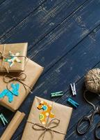 Christmas gifts in kraft paper on a dark wooden surface.