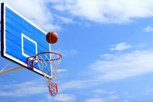 Basketball scoring goal on hoop photo