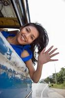 cheerful girl waving from the bus photo