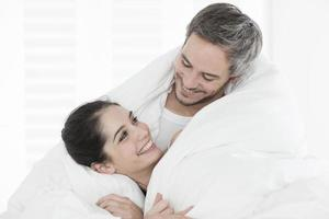 cheerful young couple wrapped in their quilt photo