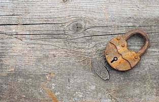 Old padlock over wooden background.With copy space