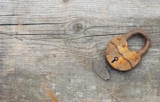 viejo candado sobre fondo de madera con espacio de copia foto