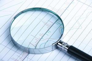 Magnifying glass with financial graph photo