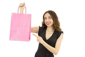 Woman pointing to shopping bag with copy space