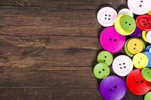 Colorful buttons on old wooden background. Copy space.
