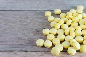 Yellow pills  on wood background with copy space photo