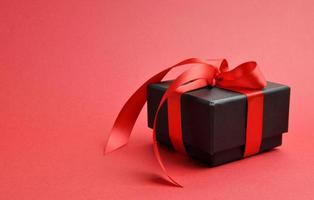 Beautiful expensive gift on red background with copy space.