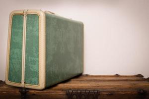 Retro, maleta sentada sobre tronco de madera, con espacio de copia foto