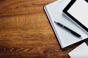 Suministros y tableta en escritorio de madera con espacio de copia