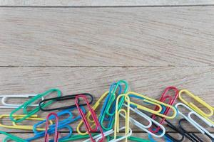 colorful paper clips on wood background with copy space photo