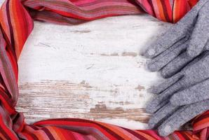 Gloves and shawl with copy space for text, wooden background