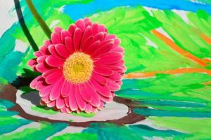 pink gerber daisy on colorful child painting with copy space photo