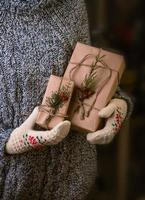 Hands in mittens holding gift box.