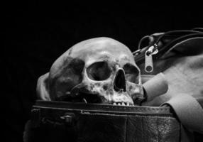 human skull are placed in old leather box photo