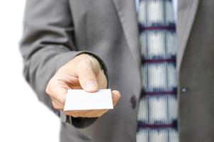 Businessman in grey suit  shows business card with copy space