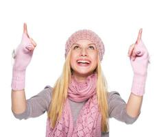 smiling girl in winter clothes pointing up on copy space