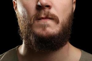 close-up do homem de barba longa e bigode em fundo escuro